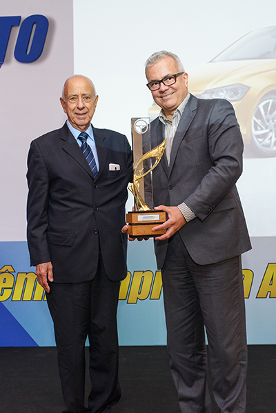 André Senador (à direita) da Volkswagen, recebe de Luiz Carlos Secco o Prêmio Carro Abiauto 2017. Abaixo, o VW Polo, modelo que faturou o prêmio máximo: Carro Abiauto 2017
